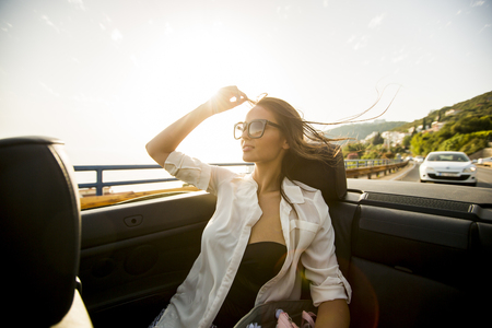 Photo pour View at young attractive woman poses in  cabriolet at seaside - image libre de droit