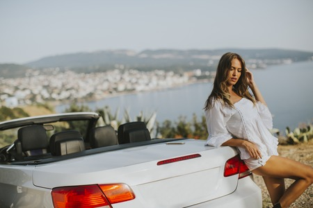Photo pour View at young attractive woman poses next to a  cabriolet at seaside - image libre de droit