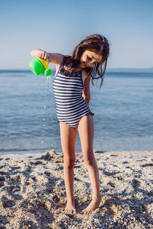 Foto de Cute little girl plaing with water on the sandy beach at summer - Imagen libre de derechos