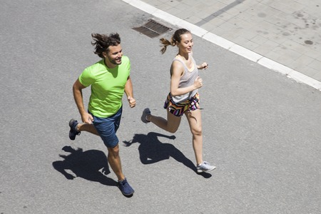 Photo pour Handsome man and beautiful woman jogging together on street at sunny day - image libre de droit
