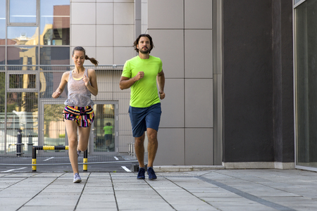 Photo pour Young couple running in the urban environment on a sunny summer day - image libre de droit