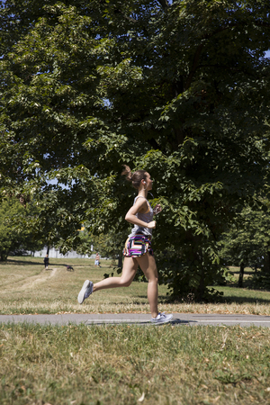 Photo pour Young woman running in the park at sunny summer day - image libre de droit
