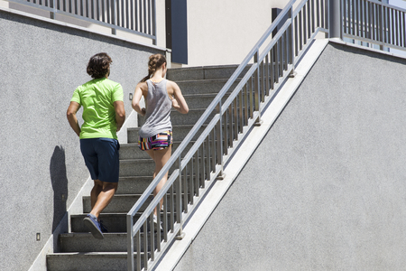 Photo pour Handsome man and beautiful woman jogging together on stairs in urban environment at sunny day - image libre de droit