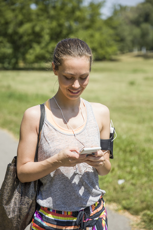 Photo pour Female runner listening music outdoor at sunny day - image libre de droit