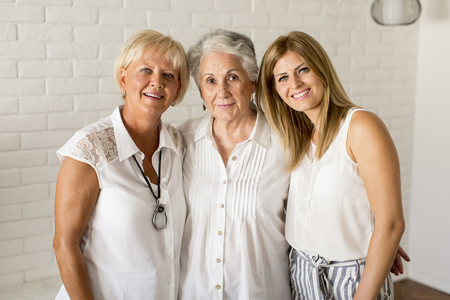 Foto de Portrait of a smiling woman , grandmother and granddaughter  at home - Imagen libre de derechos