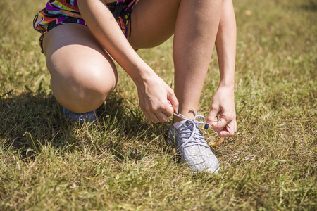 Photo pour Woman doing shoelace tying during exercise in the park - image libre de droit