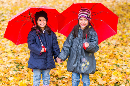 Photo for Portrait of happy little girls laughing with  umbrellas in the rain - Royalty Free Image