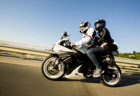 Foto de Young man and a woman on a motorcycle by day - Imagen libre de derechos