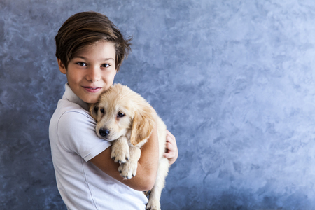 Foto de Portrait of teen boy with golden retriever by the wall - Imagen libre de derechos