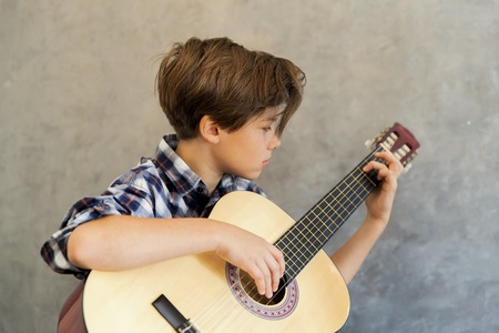 Photo for Portrait of Teen boy playing acoustic guitar - Royalty Free Image