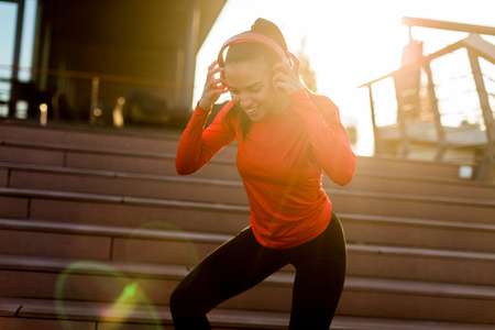 Photo pour Young attractive female runner taking break after jogging outdoors - image libre de droit