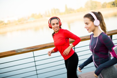 Photo pour Two young women running by the river in the morning - image libre de droit