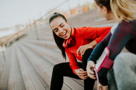 Photo pour Two young attractive female runner taking break after jogging outdoors - image libre de droit