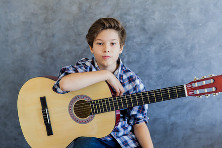 Photo pour Cute teen boy with acoustic guitar - image libre de droit