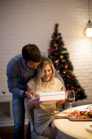 Foto de Happy young couple with present at Christmas time - Imagen libre de derechos