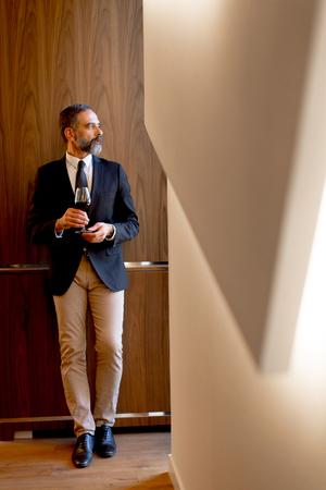Photo pour Handsome elegant businessman drinking red wine in bar - image libre de droit