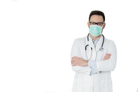 Foto de Portrait of handsome young doctor in white medical uniform and mask looking at camera against white background - Imagen libre de derechos