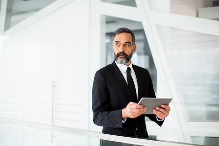 Foto de Handsome middle age businessman with digital tablet in the modren office - Imagen libre de derechos
