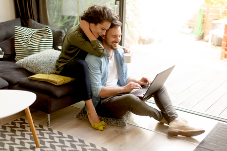 Photo pour Young couple sitting on floor and using notebook. Online shopping - image libre de droit