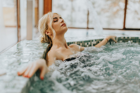 Photo pour Pretty young woman relaxing in the whirlpool bathtub - image libre de droit