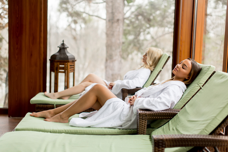 Photo pour Pretty young women relaxing on the deckchair by the swimming pool in spa - image libre de droit