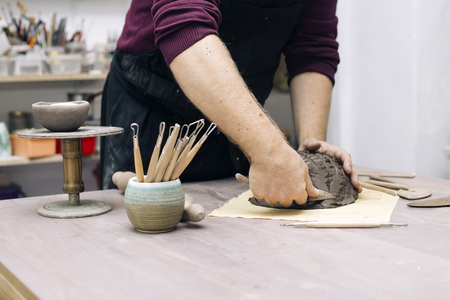 Photo pour Cllose up view at skilled master preparing clay workpieces for new his creations - image libre de droit