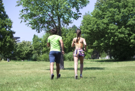 Photo pour Young couple jogging at the green environment in the summer - image libre de droit