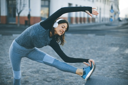 Photo pour View at young woman practices stretching after jogging outdoor - image libre de droit