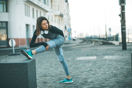 Photo pour Young sportswoman stretching and preparing to run outdoor - image libre de droit