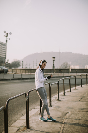 Photo pour Young female athlete taking break from running workout outdoor - image libre de droit
