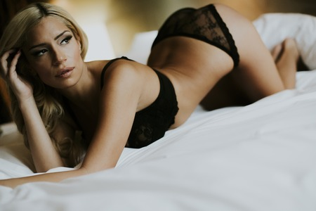 Photo for Pretty young woman lying on bed in the room - Royalty Free Image
