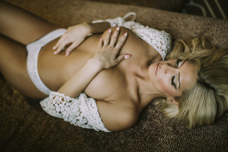 Photo for Pretty attractive young woman laying on the bed - Royalty Free Image