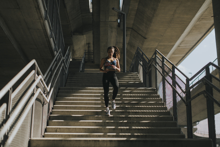Photo pour Young woman running alone down stairs  outdoor in urban environment - image libre de droit