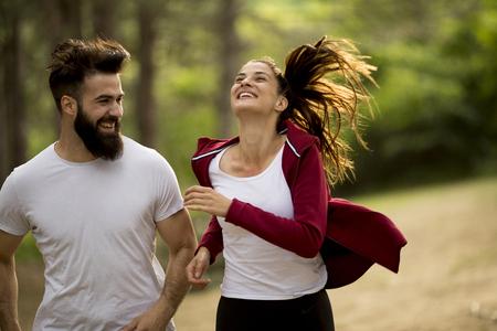 Photo pour Young couple jogging outdoors in nature - image libre de droit