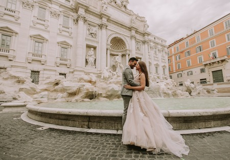 Photo pour Just married bride and groom posing in front of Trevi Fountain (Fontana di Trevi), Rome, Italy - image libre de droit