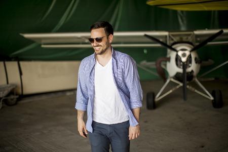 Foto de Handsome young man in the airplane hangar - Imagen libre de derechos
