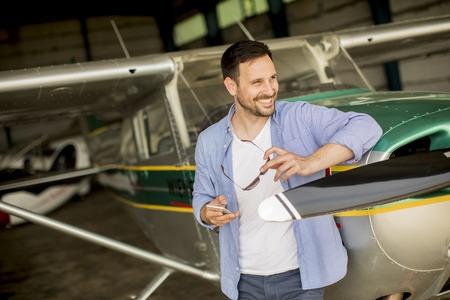 Foto de Handsome young pilot checking airplane  in the hangar - Imagen libre de derechos
