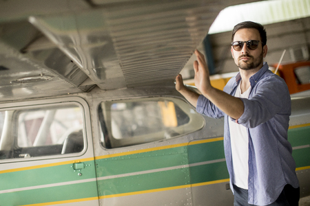 Photo for Handsome young pilot checking his ultralight airplane in the hangar before flight - Royalty Free Image