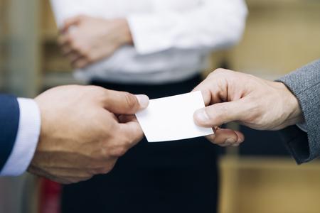 Foto de Closeup of businesspeople exchanging business card in the office - Imagen libre de derechos