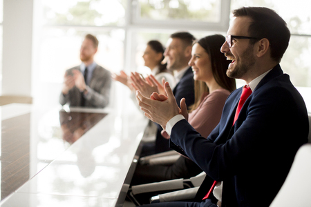 Photo for Businesspeople applauding while in a meeting at modern office - Royalty Free Image