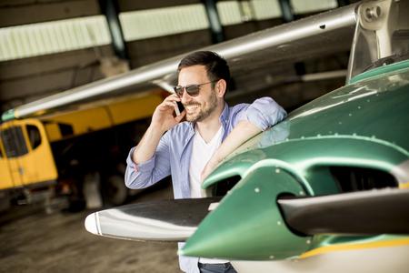 Foto de A young handsome pilot checking the airplane in the hangar and using mobile phone - Imagen libre de derechos