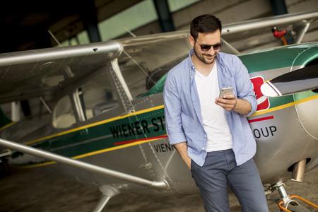 Foto de Young handsome young pilot checking airplane in the hangar and using mobile phone - Imagen libre de derechos
