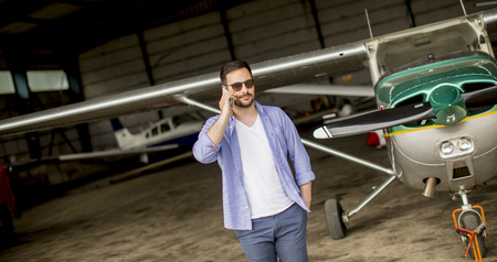 Foto de Young handsome young pilot checking airplane in the hangar and using mobile phone - Imagen libre de derechos