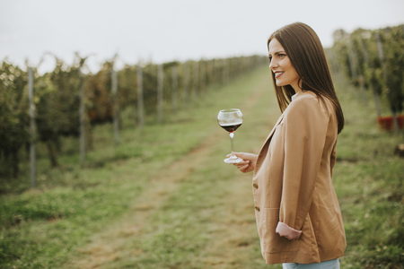 Photo for Vintner woman tasting red wine from a glass in a vineyard - Royalty Free Image