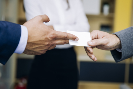Photo pour Closeup of businesspeople exchanging business card in the office - image libre de droit