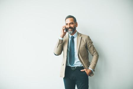 Foto de Handsome mature businessman talking on mobile phone in the office - Imagen libre de derechos