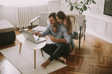 Foto de Cheerful couple searching internet and  shopping online  in living room at home - Imagen libre de derechos
