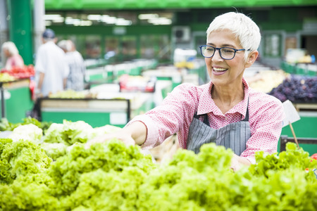 Photo for Portrait of senior woman sells lettuce on marketplace - Royalty Free Image