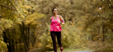 Photo pour Young fitness woman running at  forest trail in autumn - image libre de droit