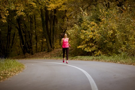 Photo pour Young fitness woman running at forest trail in golden autumn - image libre de droit